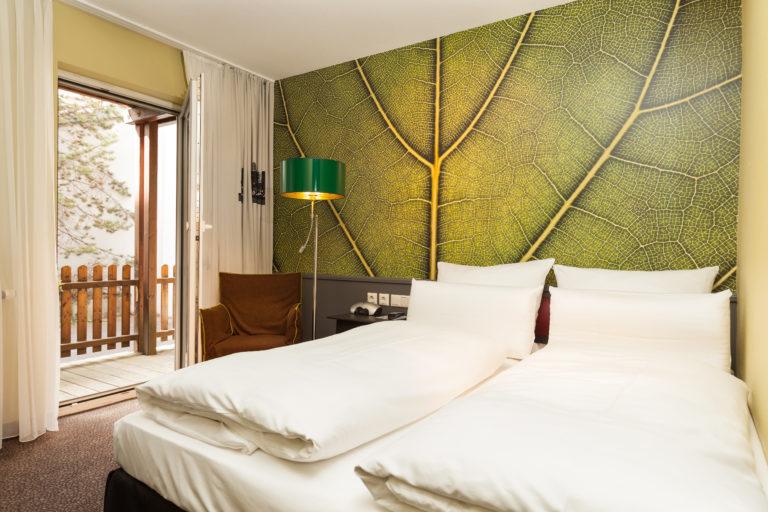 Ein gut belichtetes Hotelzimmer mit Doppelbett und Balkon im Best Western Nürnberg