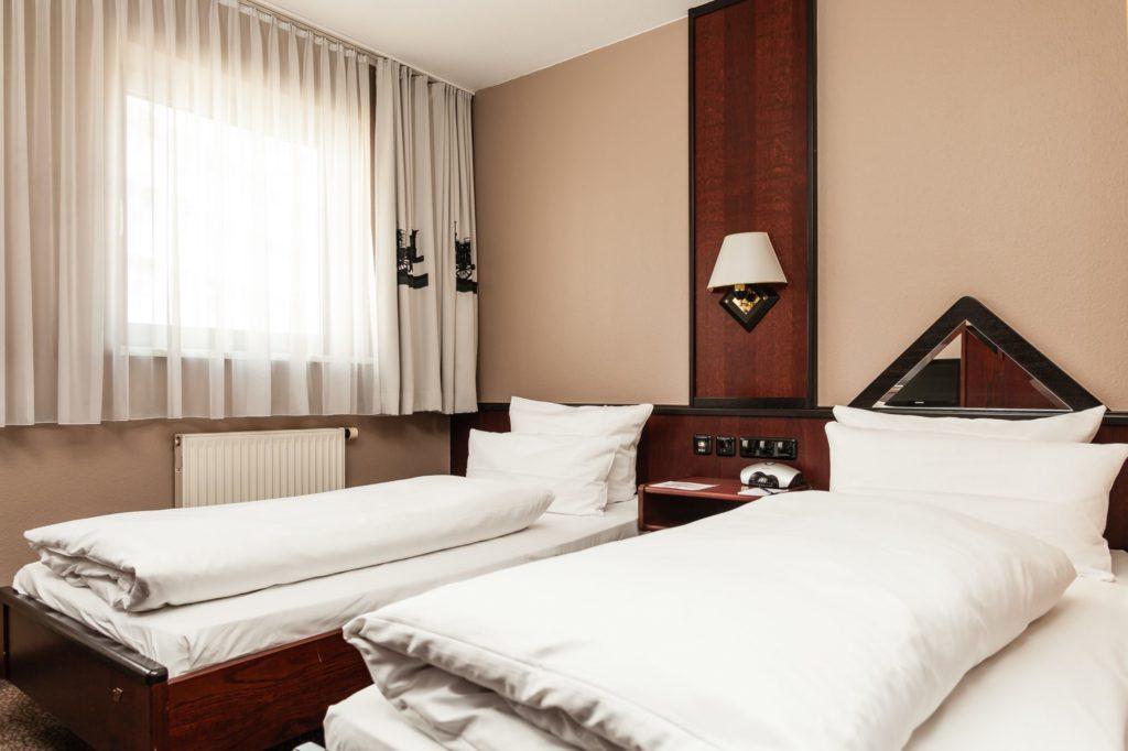 Ein helles Hotelzimmer mit zwei Betten und edelen Holzmöbeln im Best Western Nuernbeg