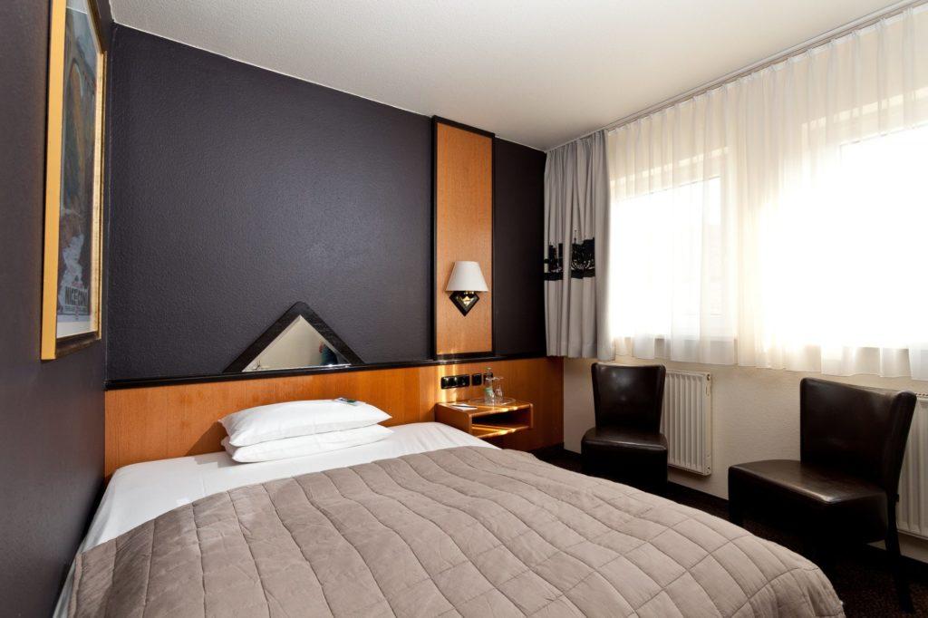 Hotelzimmer mit großem Bett und klassischem Design in nähe des Hauptnbahnhofs