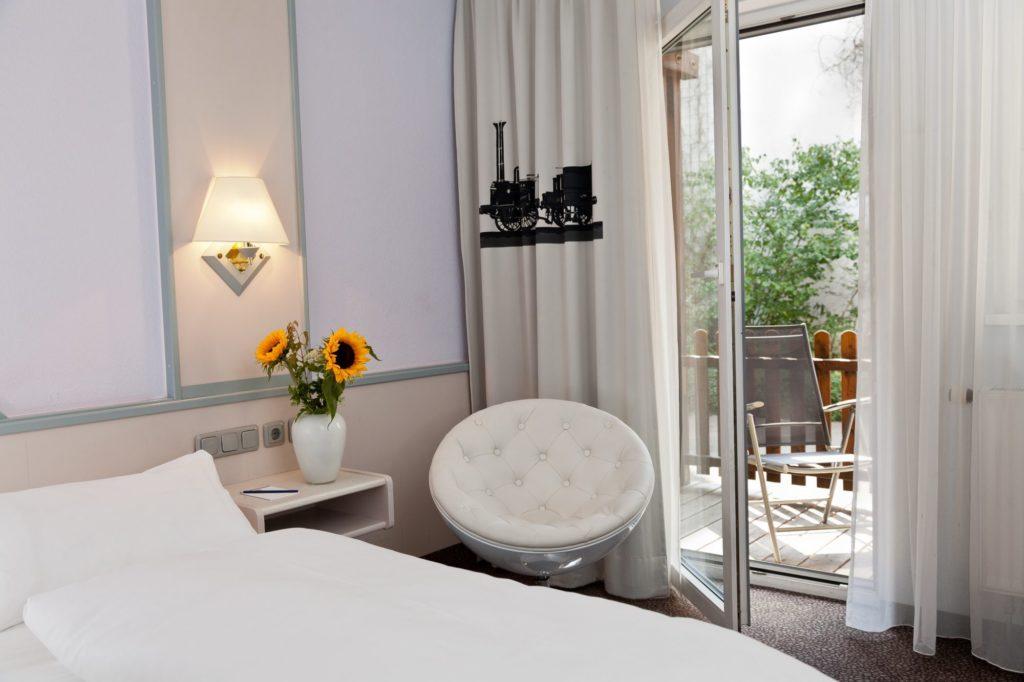 Ein Hotelzimmer in schönem Weiß und Terasse mit Sitzmöglichkeit im BW Hotel in Nuernberg